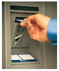 Man inserting debit card into ATM slot